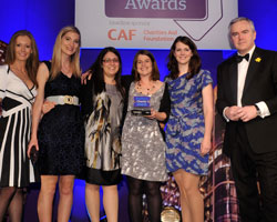 Park Publishing's Charlotte Friend [l] and Huw Edwards [r] give the award to Tesco and the Alzheimer's Society