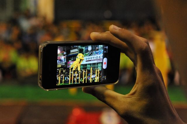 A spectator films a traditional lion dance performance on his smartphone in Yangon (2013). Myanmar is entering the digital age