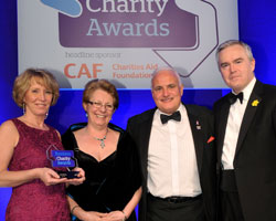 Experian community involvement manager Jan Barratt [l] and BBC News presenter Huw Edwards [r] give the award to Travis Perkins
