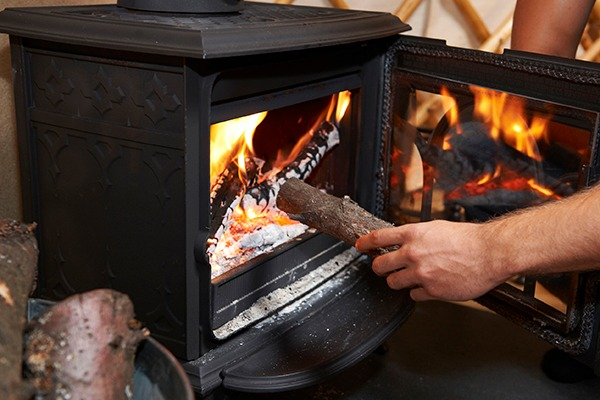 Person putting log into wood burner. Photograph: Ian Allenden/123RF