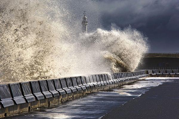 Wave crashing onto coastal road. Photograph: Designpics/123RF